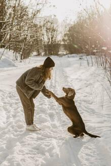 Deutschland, Brandenburg, Strausberg, Mädchen hält die Pfote von ihrem Hund in verschneiter Winterlandschaft - OJF00426